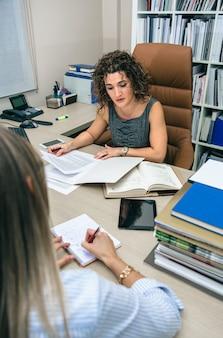 Ritratto di donna d'affari riccia che lavora con documenti in ufficio mentre segretaria bionda prende appunti taking