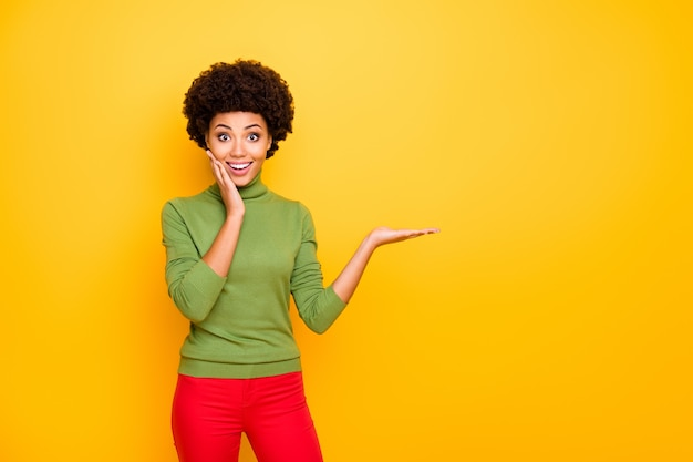 Ritratto di ricci allegra carina donna piuttosto simpatica in pantaloni rossi che tiene uno spazio vuoto a portata di mano sorridendo emotivamente a trentadue denti.