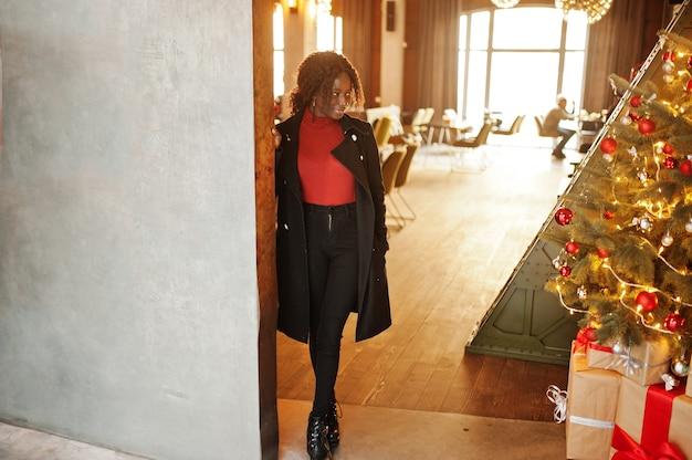 Ritratto di una donna africana dai capelli ricci che indossa un cappotto nero alla moda e un dolcevita rosso in posa contro le decorazioni dell'albero di capodanno.