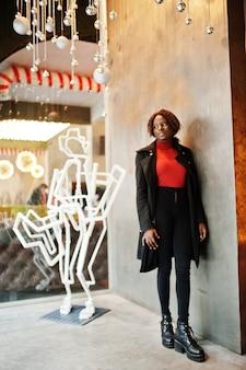 Ritratto di una donna africana dai capelli ricci che indossa cappotto nero alla moda e dolcevita rosso in posa al caffè.