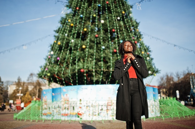 Ritratto di una donna africana dai capelli ricci che indossa cappotto nero alla moda e dolcevita rosso in posa all'aperto contro l'albero principale di capodanno della città.