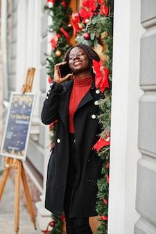 Ritratto di una donna africana dai capelli ricci che indossa cappotto nero alla moda e dolcevita rosso in posa all'aperto vicino alla porta con decorazioni natalizie, capodanno. parla per telefono.