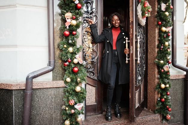 Ritratto di una donna africana dai capelli ricci che indossa cappotto nero alla moda e dolcevita rosso in posa all'aperto vicino alla porta con decorazioni natalizie, capodanno.