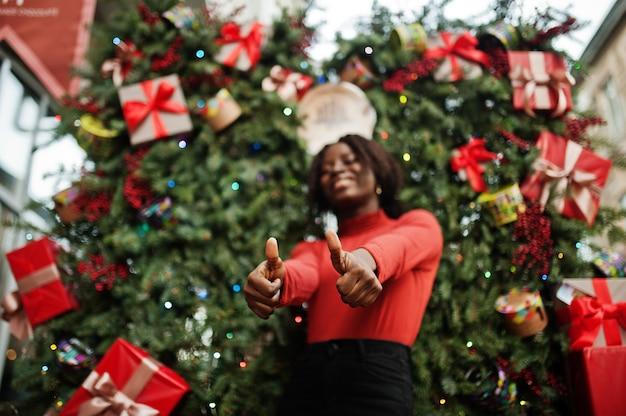 Ritratto di una donna africana dai capelli ricci che indossa dolcevita rosso alla moda in posa contro le decorazioni natalizie, tema della vigilia di capodanno. mostra pollice in alto.