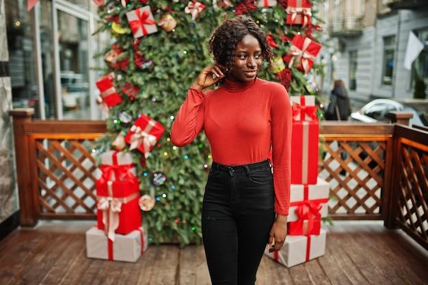 Ritratto di una donna africana dai capelli ricci che indossa dolcevita rosso alla moda in posa contro le decorazioni natalizie, tema della vigilia di capodanno.