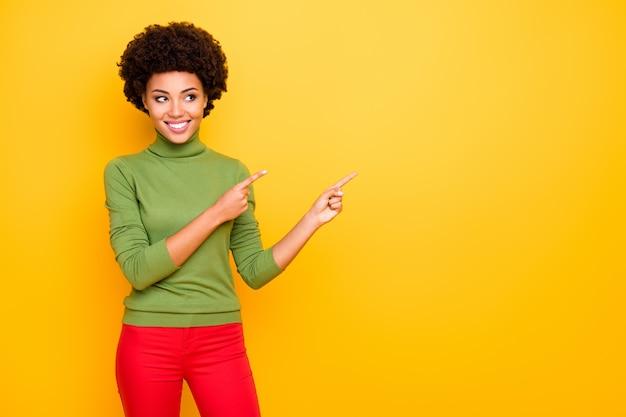 Il ritratto della donna positiva allegra ondulata riccia con gli indici ha indicato lo spazio vuoto in pantaloni rossi che mostrano conto da seguire.