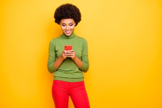 Ritratto di ricci ondulati allegra alla moda carina bella bella ragazza in pantaloni rossi navigazione telefono sorriso a trentadue denti.