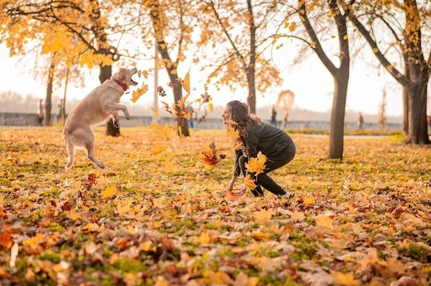 Ritratto di una giovane donna riccia che abbraccia il suo cane golden retriever nel parco autunnale. sfondo di foglie gialle. giovane donna riccia seduta con il suo cane in foglie d'autunno