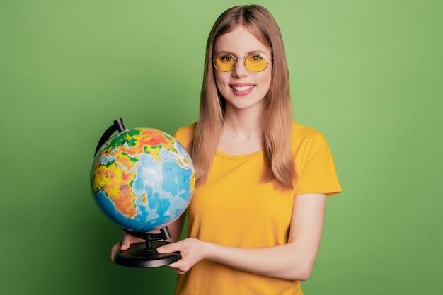 Il ritratto di una simpatica e adorabile signora turistica tiene il globo dimostrando l'opzione di viaggio indossando una maglietta gialla con occhiali da sole