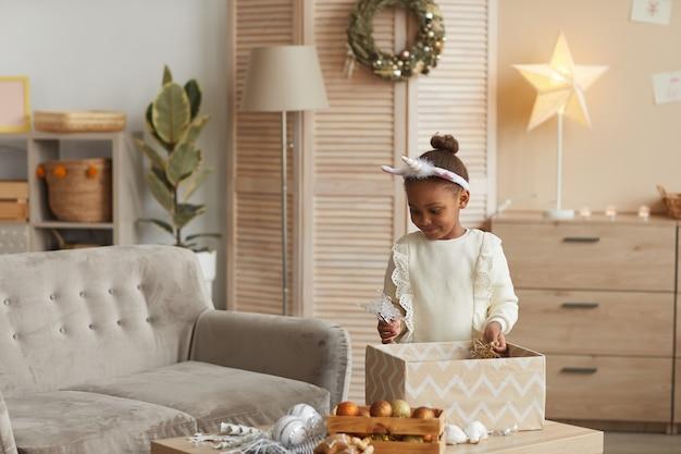 Ritratto di ragazza carina afro-americana apertura confezione regalo in interni accoglienti, concetto di sorpresa di natale e compleanno, copia dello spazio