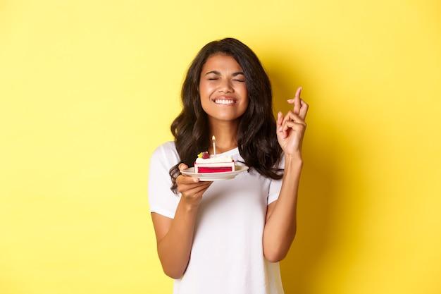 Ritratto di donna afro-americana carina, chiudere gli occhi e sorridere, incrociare le dita per esprimere un desiderio sulla torta di compleanno, festeggiare il compleanno, in piedi su sfondo giallo