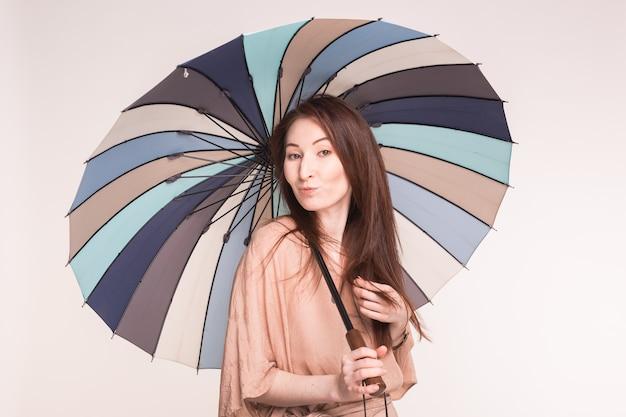 Ritratto di donna asiatica carina sotto l'ombrello a strisce sul muro bianco