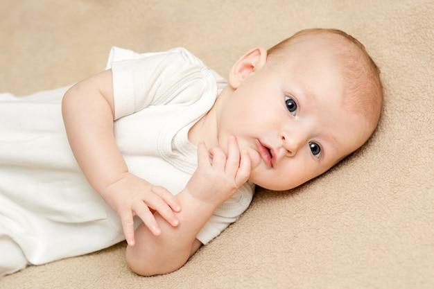 Un neonato sveglio del ritratto in vestiti bianchi che si trovano su un letto beige