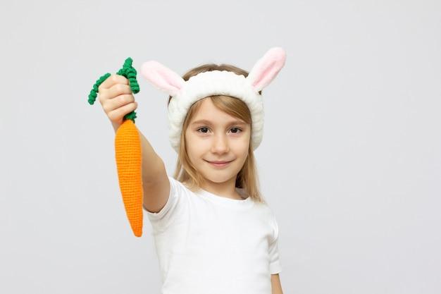Ritratto di un bambino carino vestito con orecchie da coniglio con una carota