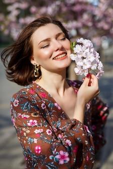 Ritratto di una ragazza carina e bella donna in un vestito in giardino nel mezzo di sakura in fiore. primavera e tempo di sole. sfondo sfocato e messa a fuoco selezionata.