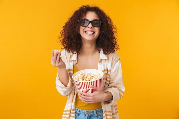 Il ritratto di una bella giovane donna riccia sveglia che posa isolata sulla parete gialla con gli occhiali mangia popcorn guarda film.