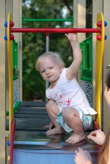 Ritratto di carino bambino biondo nel parco giochi. bambino a piedi nudi su una diapositiva. cornice verticale.