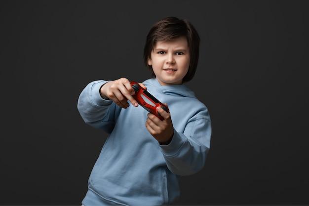 Ritratto di ragazzo carino 10-12 anni, vestito in abiti casual, in piedi con il joystick in mano giocando
