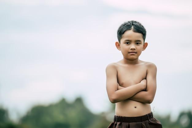 Ritratto di ragazzo carino senza camicia in abito tradizionale tailandese in piedi e braccia incrociate sul petto
