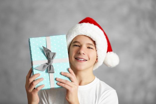 Ritratto di ragazzo carino con scatola regalo blu, primo piano