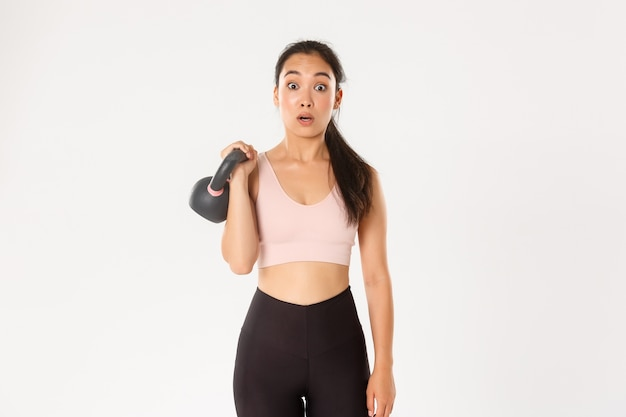 Ritratto di ragazza carina bruna asiatica fitness, iscriviti a lezioni di bodybuilding in palestra, sorpreso dal peso del kettlebell, in piedi su sfondo bianco.