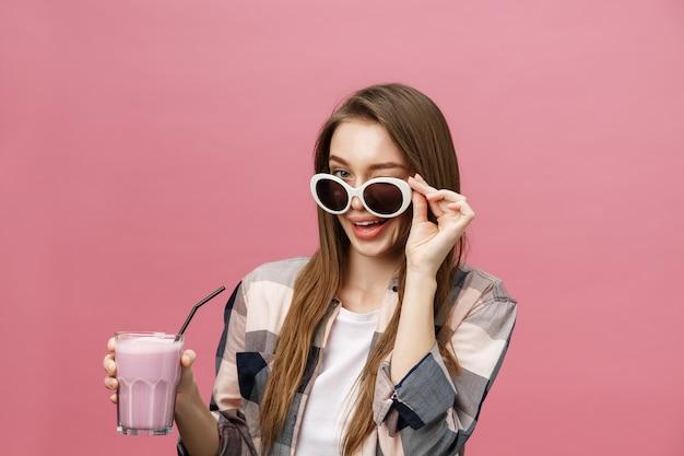 Ritratto di una ragazza carina casual che beve succo d'arancia