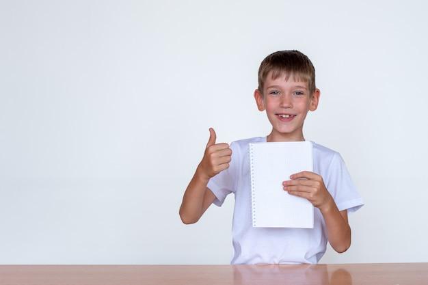 Ritratto di un simpatico ragazzo caucasico che tiene in mano un taccuino bianco, mostrando i pollici in su. ragazzo a un tavolo luminoso su sfondo bianco. concetto per il ritorno a scuola, gioia, felicità. copia spazio