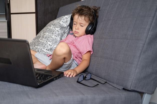 Ritratto di un simpatico ragazzo caucasico stanco che dorme mentre usa il computer portatile e indossa grandi occhiali e cuffie mentre studia a casa, concetto di educazione remota. quarantena. torna al concetto di scuola.