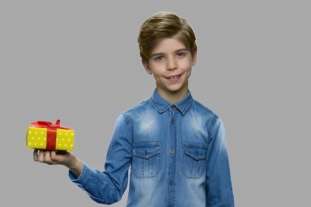 Ritratto di ragazzo carino bambino in posa con confezione regalo. ragazzino bello che tiene la casella attuale e che guarda l'obbiettivo. felice concetto di vacanza.