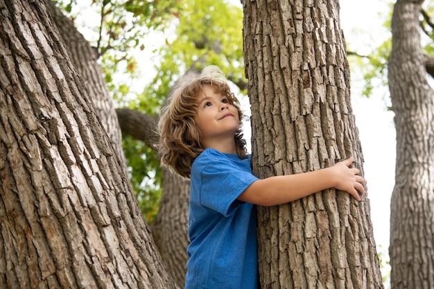 Ritratto di un bambino carino che si arrampica su un albero in un parco