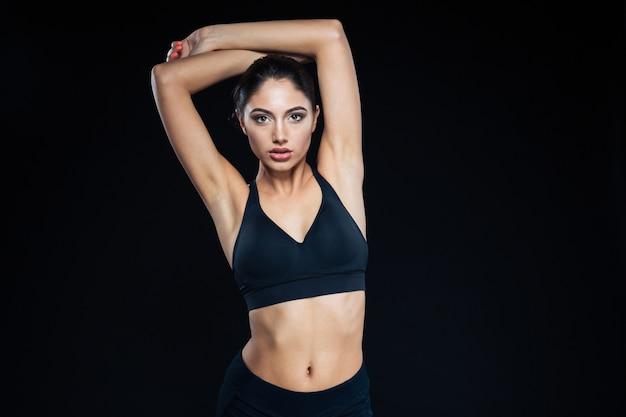 Ritratto di una donna carina fitness in posa su sfondo nero