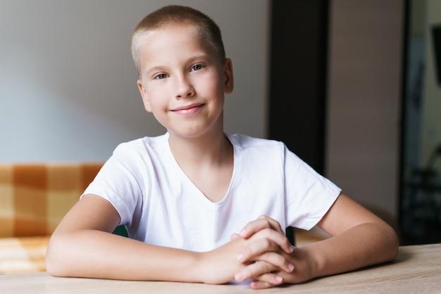 Ritratto di un simpatico scolaro della generazione z in maglietta bianca che parla con la webcam durante la videochiamat...