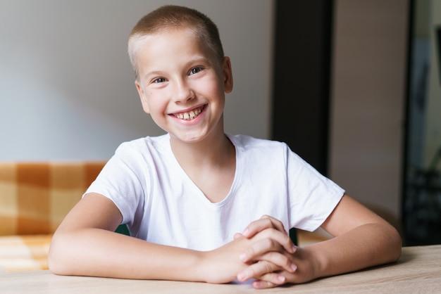 Ritratto di un simpatico scolaro della generazione z in maglietta bianca che parla con la webcam durante la videochiamata bambino st