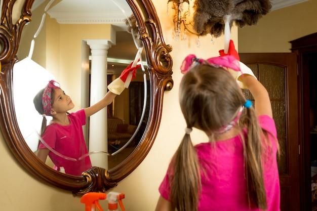 Ritratto di ragazza carina che pulisce specchio e lampada con pennello