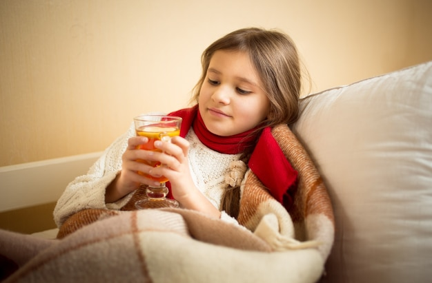 Il ritratto di una ragazza carina ha l'influenza e tiene una tazza di tè a letto