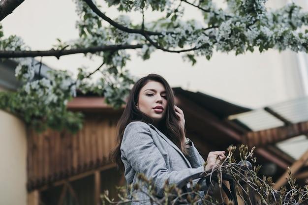 Ritratto di ragazza carina in giacca con lunghi capelli ricci in città