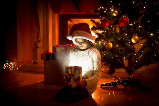 Ritratto di ragazza carina seduta sul pavimento e con in mano una scatola regalo
