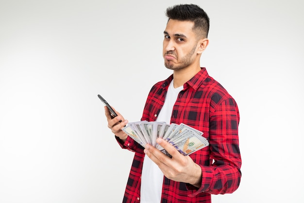 Ritratto di un ragazzo carino con un mucchio di soldi, parlando al telefono su uno studio bianco con spazio di copia