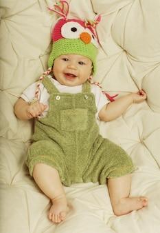 Ritratto del neonato di 5 mesi felice sveglio con il cappello divertente. foto di una ragazza divertente.