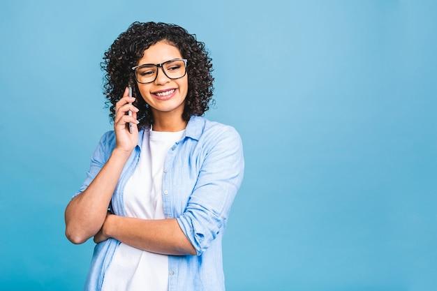 Ritratto di una ragazza nera afroamericana felice carina in casual parlando al telefono cellulare e ridendo isolate su sfondo blu.