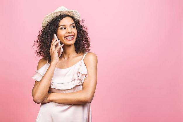 Ritratto di un simpatico felice afro american girl in abito parlando al telefono cellulare e ridendo isolate su sfondo rosa.