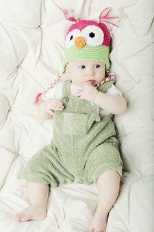 Ritratto del neonato felice sveglio con il cappello divertente