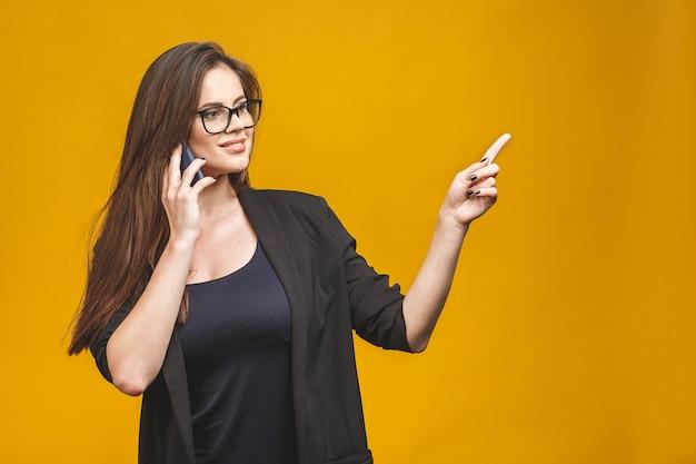 Ritratto di una ragazza carina felice di affari nella conversazione casuale sul telefono cellulare, che indica e che mostra e che ride isolato sopra la parete gialla. Foto Premium