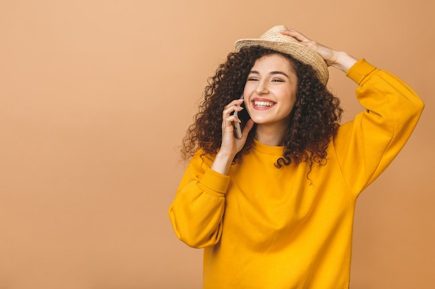 Ritratto di una ragazza carina felice studente riccio in casual parlare sul telefono cellulare e ridere isolato su sfondo beige.