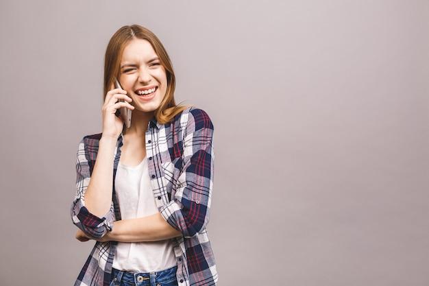 Ritratto di una ragazza felice carina in casual parlando sul cellulare e ridendo.