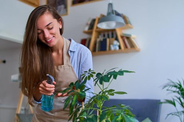 Ritratto di carino felice giovane donna attraente in grembiule irrigazione piante d'appartamento utilizzando la bottiglia spray