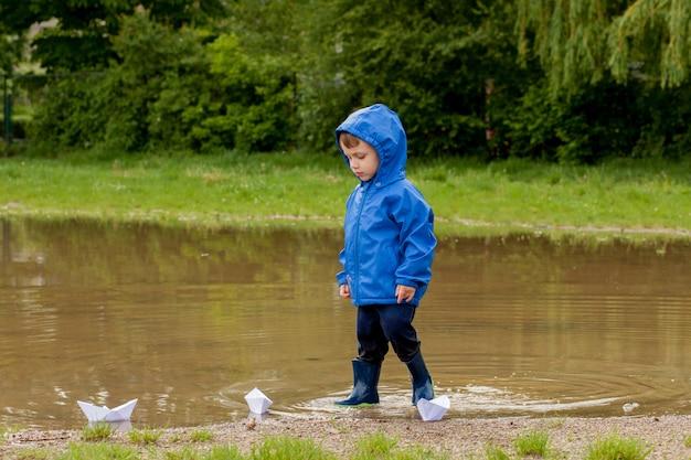 Ritratto del ragazzo sveglio del bambino che gioca con la nave fatta a mano. ragazzo dell'asilo che naviga su una barca giocattolo in riva al mare nel parco.