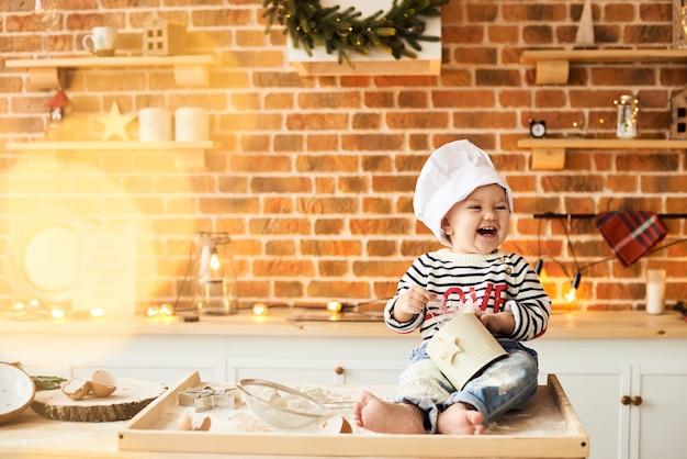 Un ritratto di ragazzo carino cucinato e giocato con farina e impasto in cucina