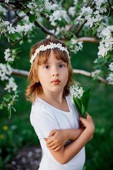 Ritratto di ragazza carina bambino 5-6 anni azienda fiore in piedi nel giardino primaverile in fiore, indossando abiti bianchi e ghirlande floreali all'aperto, la stagione primaverile sta arrivando.