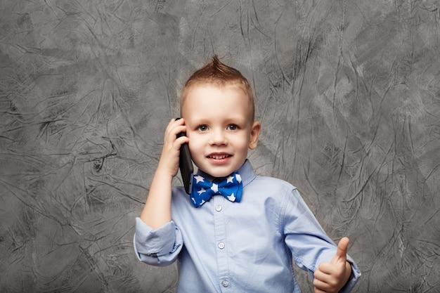 Ritratto di un ragazzino sveglio in camicia blu e farfallino con il telefono cellulare contro il grigio strutturale in studio